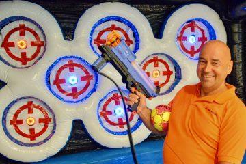 Mann med ball og lasergevær står foran blinktavle, et av mange underholdningsprodukter fra Action Brekstad